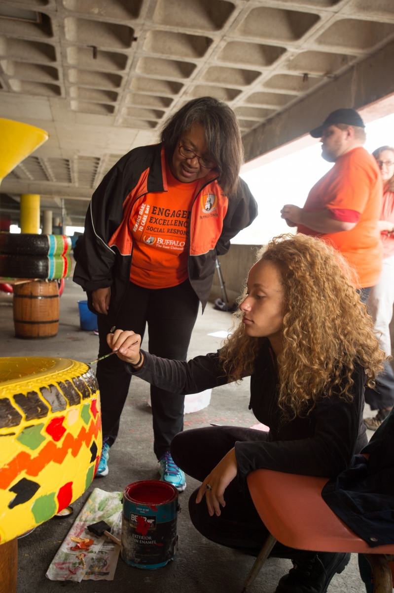 a woman paints a tire with president conway-turner looking on