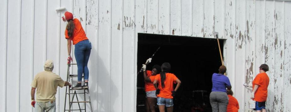 Seven people are painting a barn white