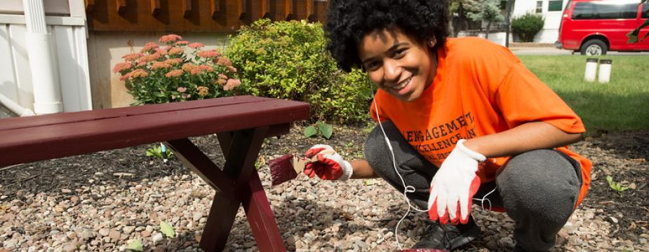 A female student in an orange t-shirt is squatting down as she paints a picnic bench a dark red color.  A can of paint in the foreground and a paint brush is in her hand.