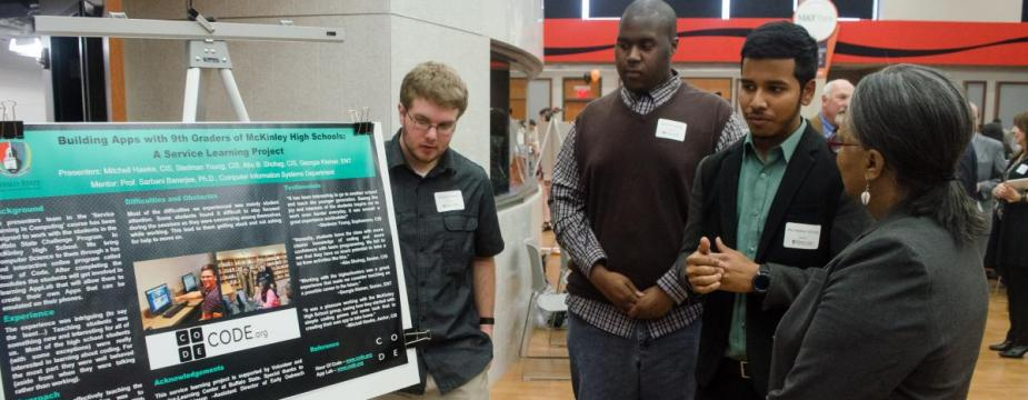 three men and one woman are standing in front of a stand holding a sign for a service learning project.