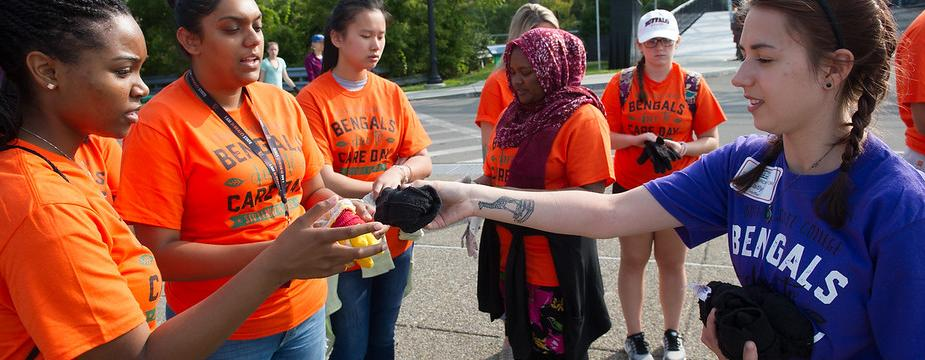 Bengals Dare to Care student leader handing a pair of gloves to female volunteers.