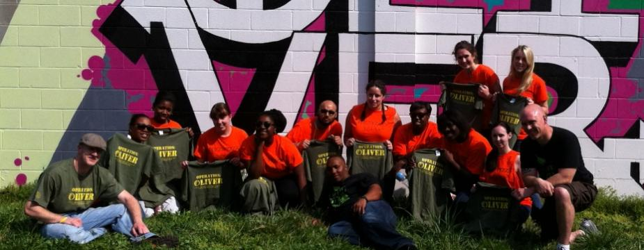 14 men and women wearing green or orange colored shirts are sitting infront of a colorful piece of artwork on the side of a building which reads OLIVER.