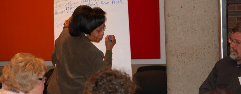 one woman is writing on a big tearoff piece of paper with others watching.