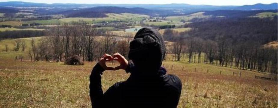 a person is standing in a field facing away from the camera making a heart with their hands.