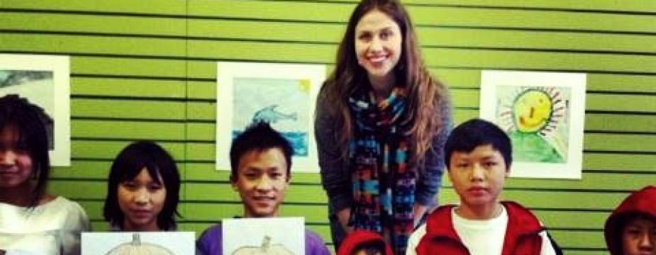 Female instructor posing with 6 students. Students are holding up drawings of jack-o-lanterns.