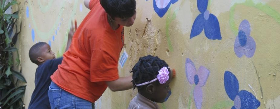 A woman and 2 kids scrub a wall