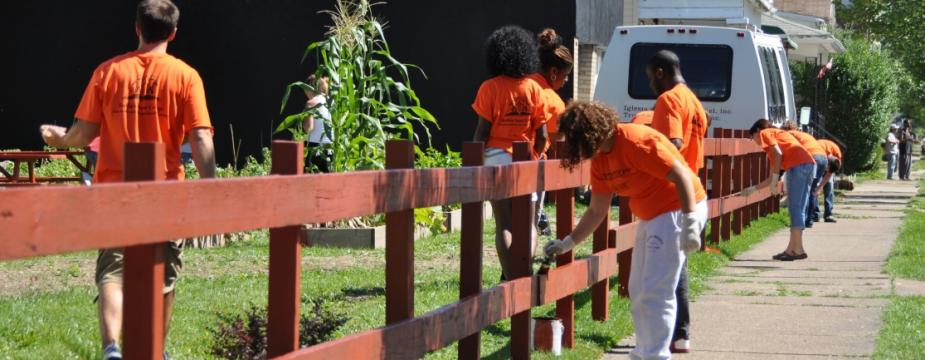 12 people are seen in this photo. many of them are wearing orange shirts and are painting a wooden fence.