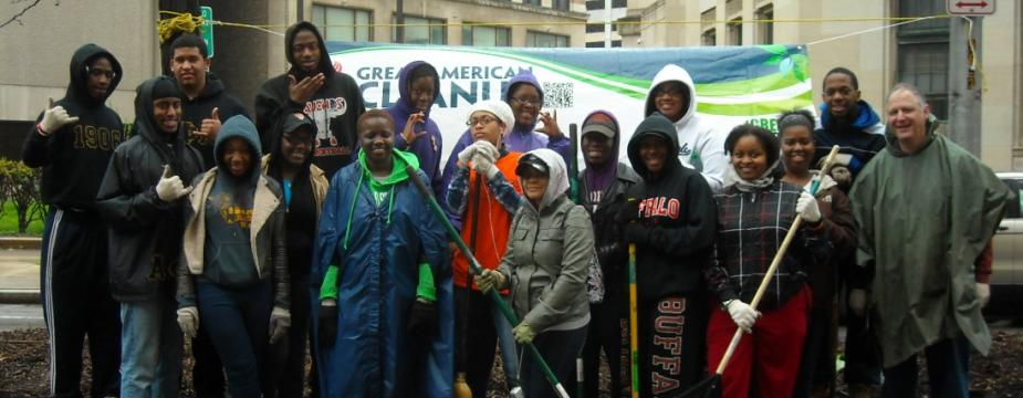 18 men and women are standing infront of a banner. A few of the people are holding rakes and brooms.