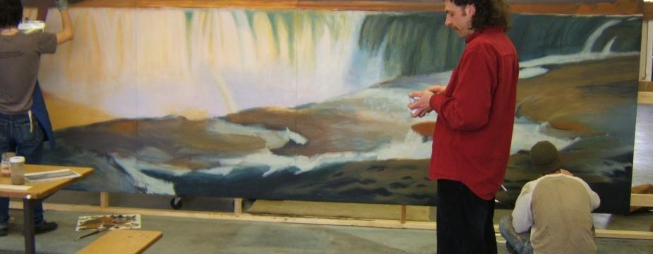a man in a red shirt is standing in front of two men painting a picture of the falls