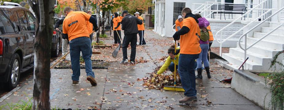 nine men and women a raking, sweeping, and picking up leaves off a sidewalk.