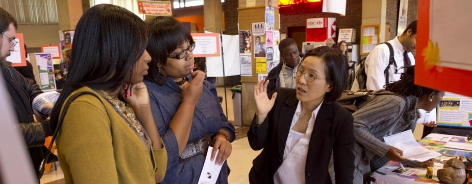 there is a room filled with people and signs. The photo is focused on a group of three women two of which are listening the third is speaking