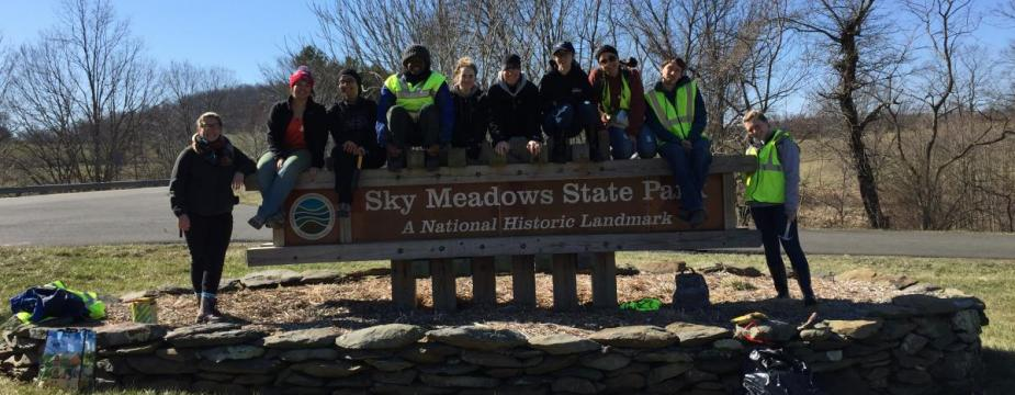 """Group of 10 people posing at Sky Meadows State Park, 8 people are standing on """"Sky Meadows State Park National Historic Landmark"""" sign, 2 people are on either side of the sign."""