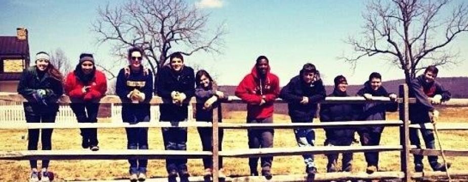 10 people, 6men and 4 women, are standing on a fence with a house, trees, and open area in the background.