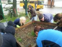 7 people are attempting to pick up a wooden box filled with soil grass and hay
