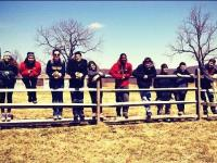 10 Alternative break participants pose for a photo on a fence in front of an open field