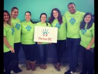"Alternative Break participants pose for a photo holding a ""thrive DC"" sign"