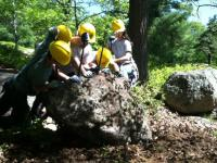 5 alternative break participants are working on moving a huge rock