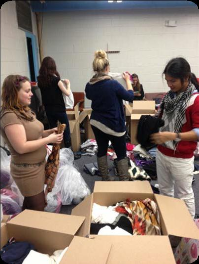 group of women opening boxes filled with clothes