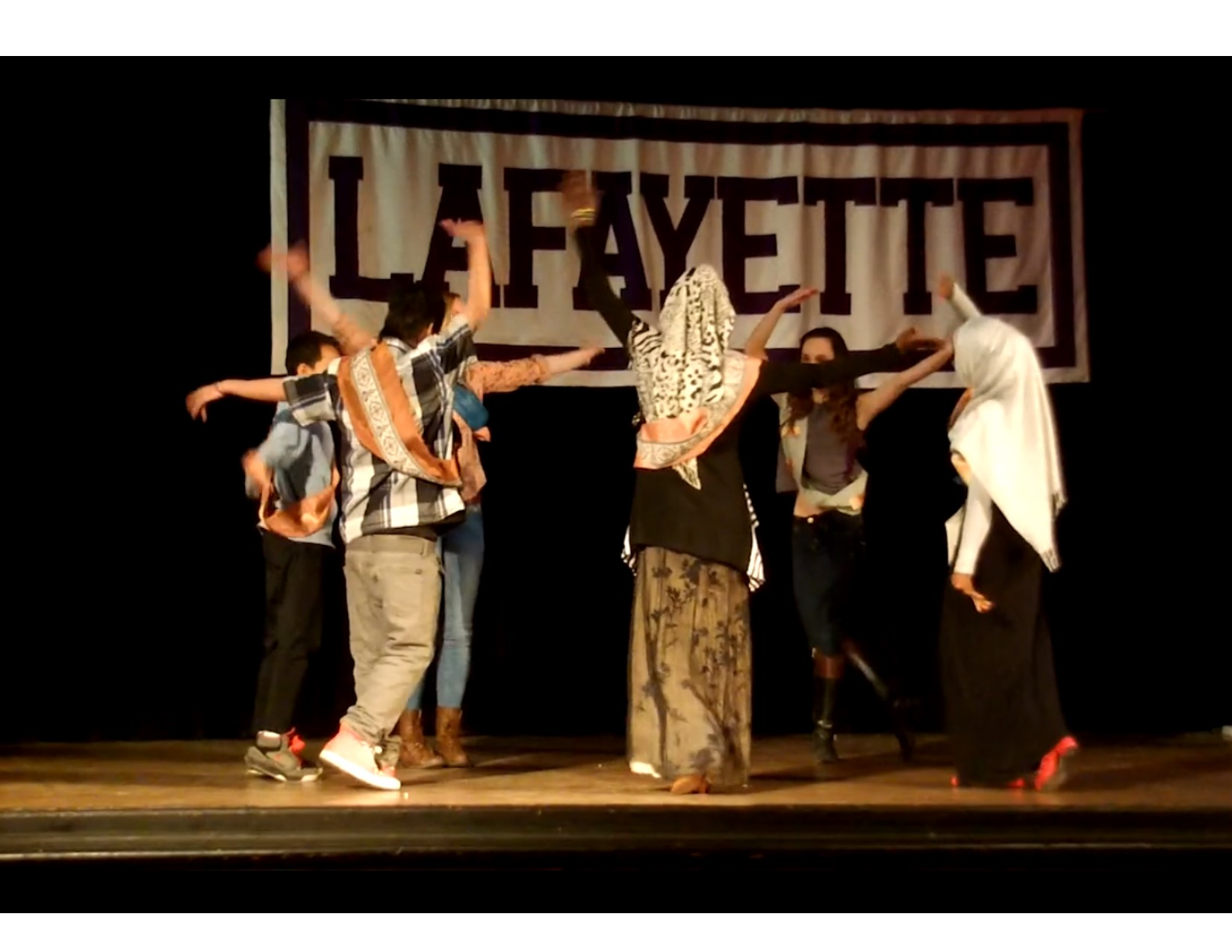 students dancing on stage in front of a lafayette banner